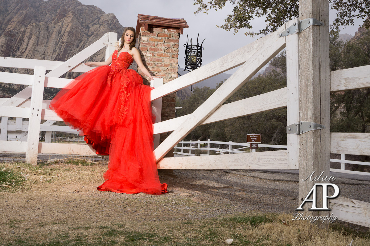 Quinceañera Photography. This photograph is showing a Quinceañera with a beautiful red dress. La Quinceañera is sitting on a wood corral door.
