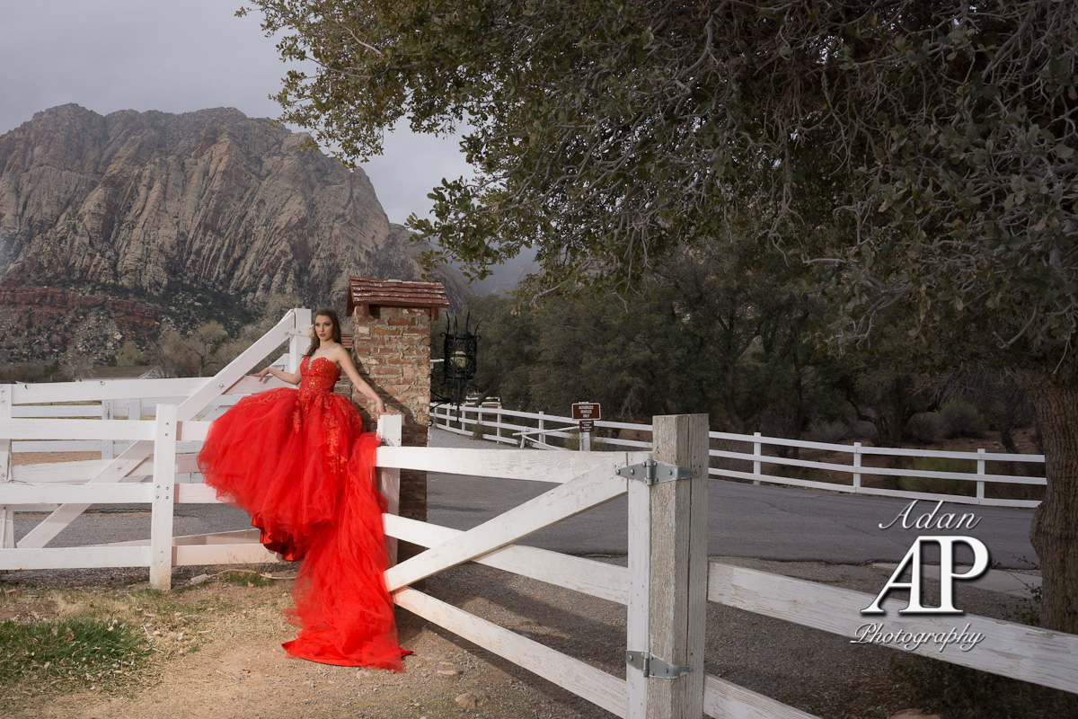 This photograph is showing a Quinceañera with a red dress. She has the arms open holding herself. La Quinceañera is sitting on a wood corral door. Forground showing a tree and background showing a mountain.