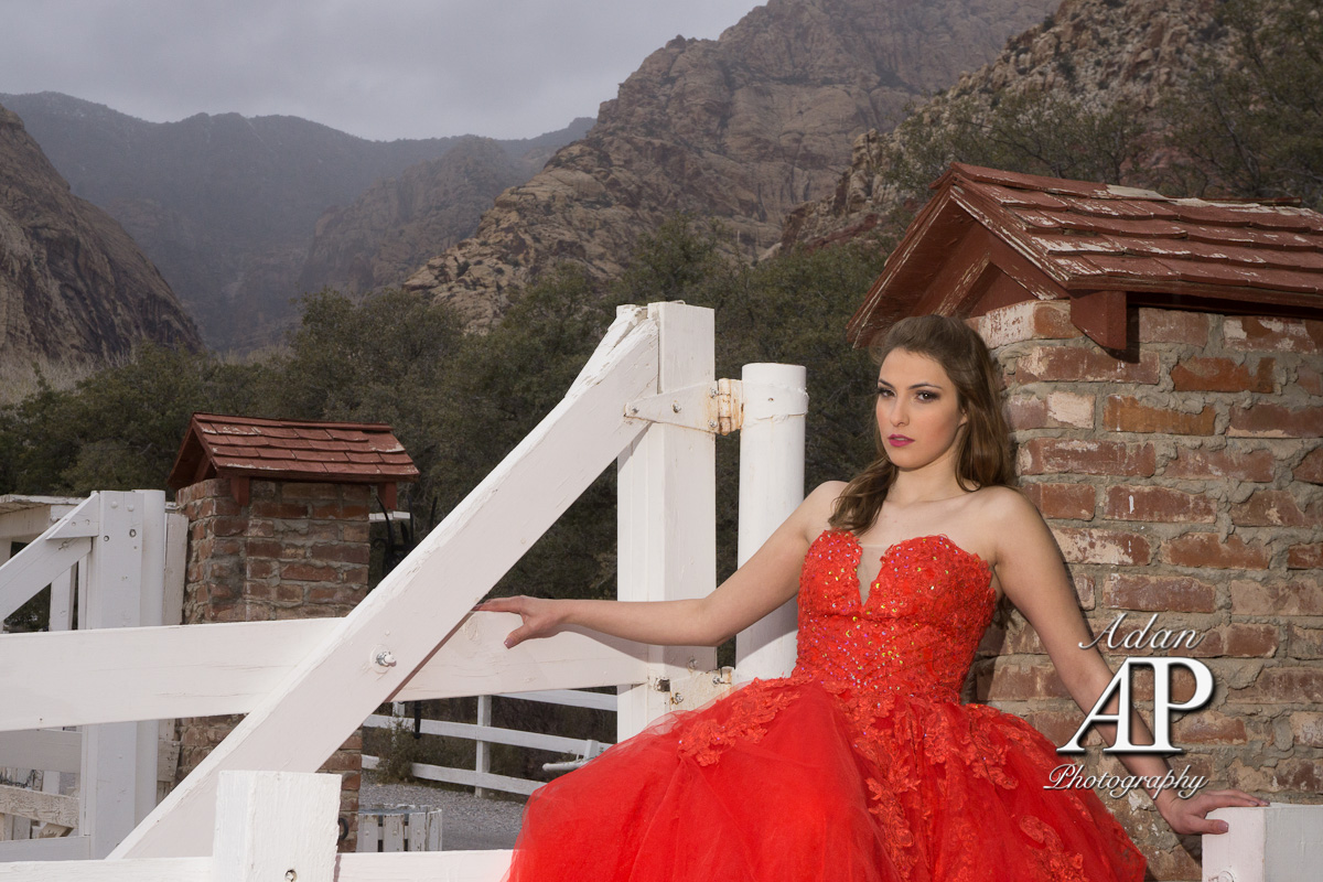 Quinceañera Photography. This photograph is showing a Quinceañera with a red dress. She has the eyes looking streight at the camera while holding her self with her arms. La Quinceañera is sitting on a wood corral door.